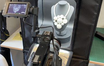 A photo showing the set-up of jewellery in a light box and a camera pointing at it.